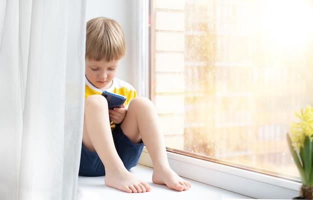 Niño pequeño con smartphone en el alféizar de la ventana, espacio para texto. concepto - cuarentena, peligro de internet.