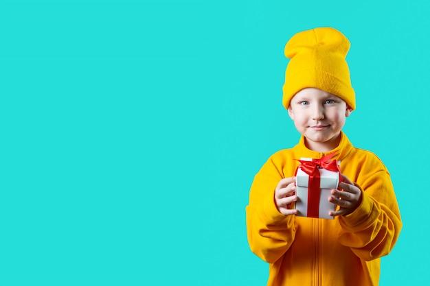 Un niño pequeño con sombrero amarillo y chaqueta con un regalo sobre un fondo de menta