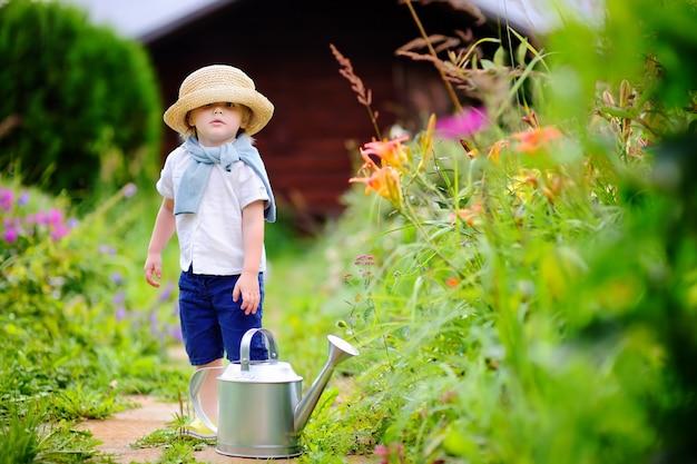 Niño pequeño con sombrero de paja, regar las plantas en el jardín