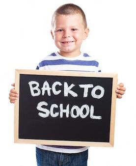 Niño pequeño sonriendo con una pizarra negra con el mensaje