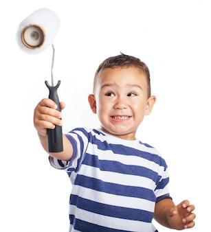 Niño pequeño sonriendo y sujetando en alto un rodillo de pintura