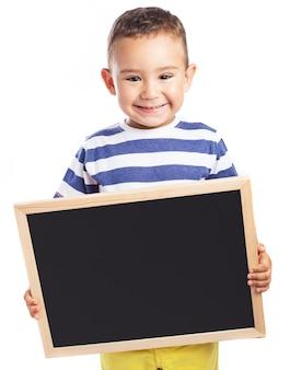 Niño pequeño sonriendo sujetando una pizarra negra