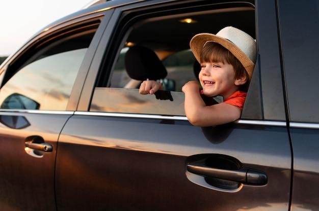 Niño pequeño sonriente en coche