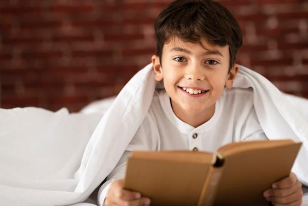 Niño pequeño sonriente que lee en casa