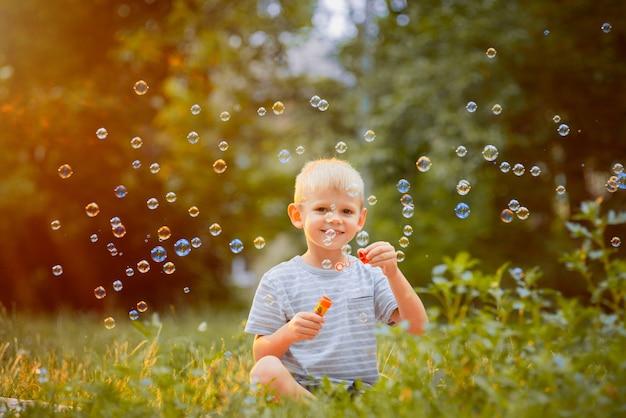 Un niño pequeño sopla pompas de jabón en un césped verde en los rayos del sol