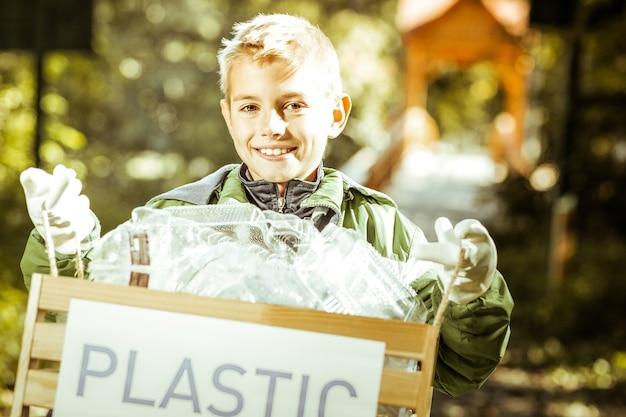 Un niño pequeño sosteniendo una caja de basura plástica en el bosque en un día soleado