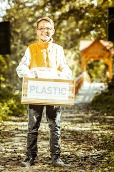 Un niño pequeño sosteniendo una caja de plástico para reciclar en un buen día.