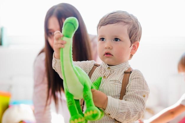 Niño pequeño sosteniendo el juguete verde del dinosaurio
