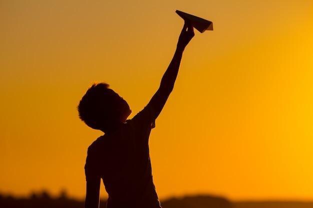 El niño pequeño sostiene un aeroplano de papel en su mano en la puesta del sol. un niño levantó su mano hacia el cielo y juega con el origami por la noche en la calle.