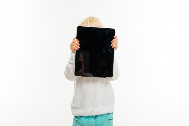 El niño pequeño sostiene una tableta con una pantalla en blanco al nivel de la cabeza sobre un fondo blanco aislado