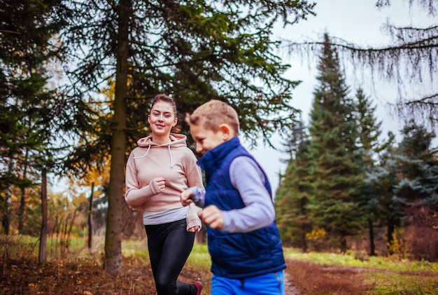 Niño pequeño y su hermana corriendo en el bosque de otoño
