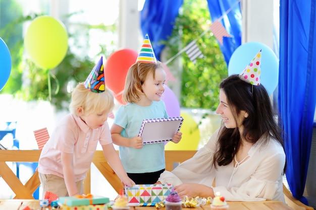 El niño pequeño y su madre celebran la fiesta de cumpleaños con decoración colorida y pasteles con decoración colorida y pastel