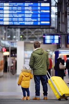 Niño pequeño y su padre en el aeropuerto internacional o en la plataforma de la estación de trenes que buscan en la pantalla de información