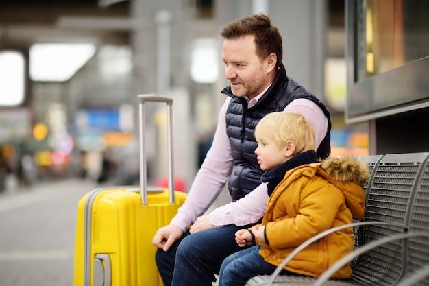 Niño pequeño y su padre esperando el tren expreso en la plataforma de la estación de ferrocarril o esperando su vuelo en el aeropuerto