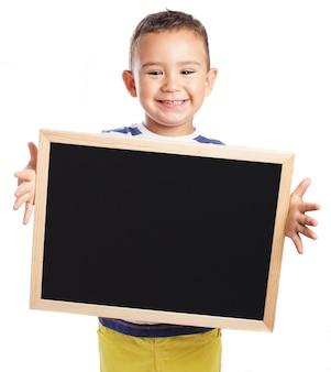 Niño pequeño sujetando una pizarra negra