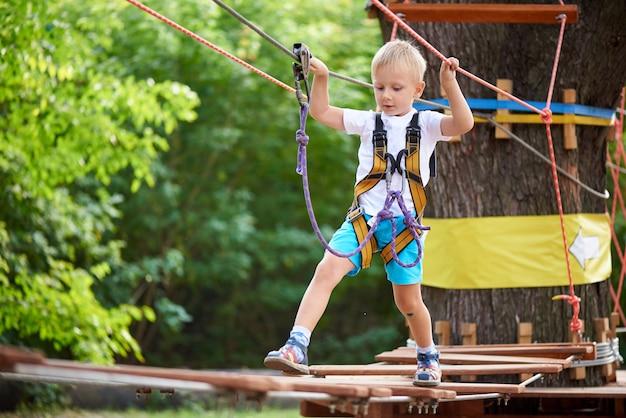 Niño pequeño supera un obstáculo en un parque de diversiones