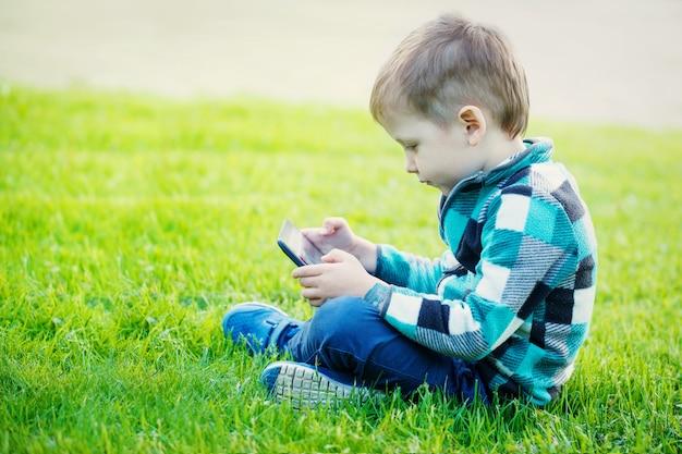 El niño pequeño con la tableta se sienta en la hierba