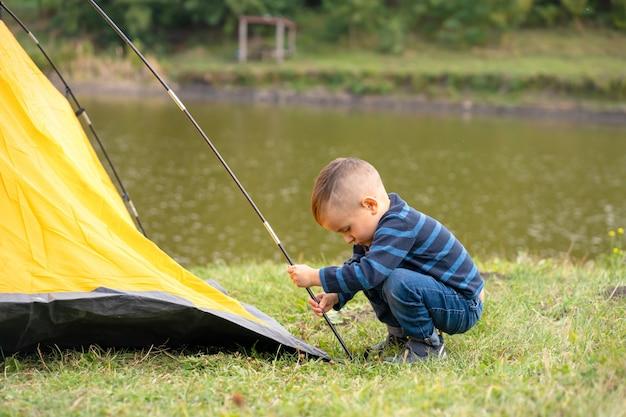 Niño pequeño en una tienda de campaña, camping en la naturaleza.