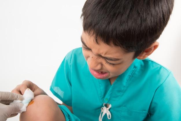 El niño pequeño tiene dolor en las piernas por dolores musculares en la rodilla
