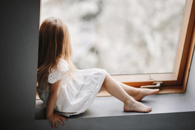 Niño pequeño en tierno vestido blanco está sentado en el alféizar de la ventana