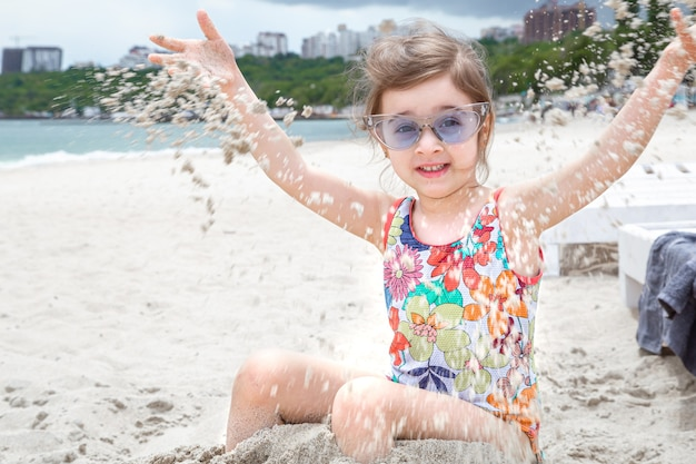 Niño pequeño tirando la arena a la orilla del mar. entretenimiento y recreación de verano.