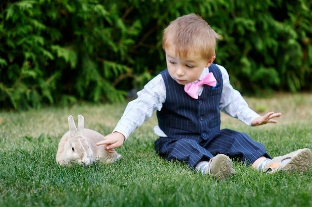 Niño pequeño en un traje jugando con un conejo en la hierba