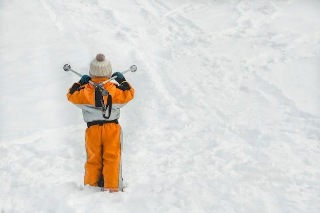 Niño pequeño en traje naranja está de pie con bastones de esquí.