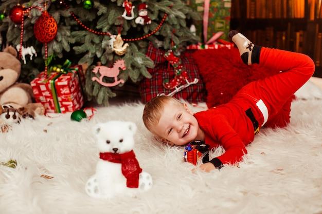 Niño pequeño en traje rojo festivo juega antes de un árbol de navidad