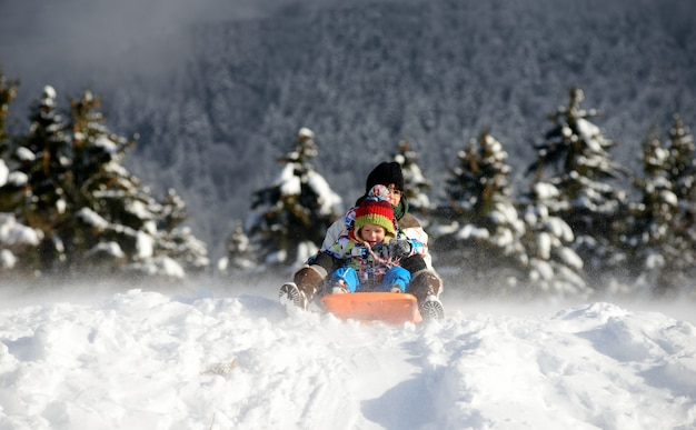 Un niño pequeño en trineo en la nieve.