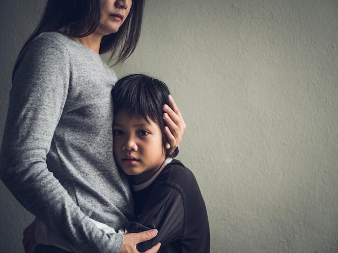 Niño pequeño triste abrazado por su madre en casa. amor, concepto de familia.