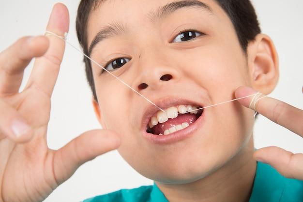 Niño pequeño usando hilo dental para limpiar el diente