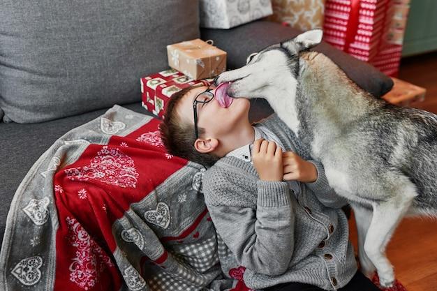 Niño con perro cerca del árbol de navidad sobre fondo de navidad