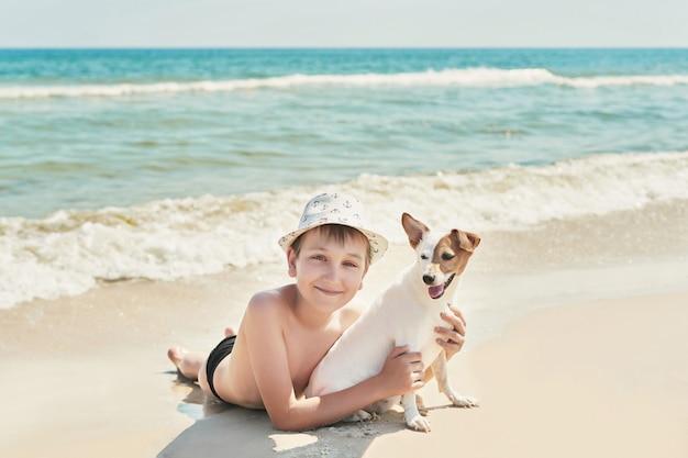 Niño con perro jack russel en la playa