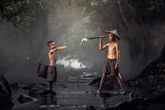 Niño pescando en arroyos