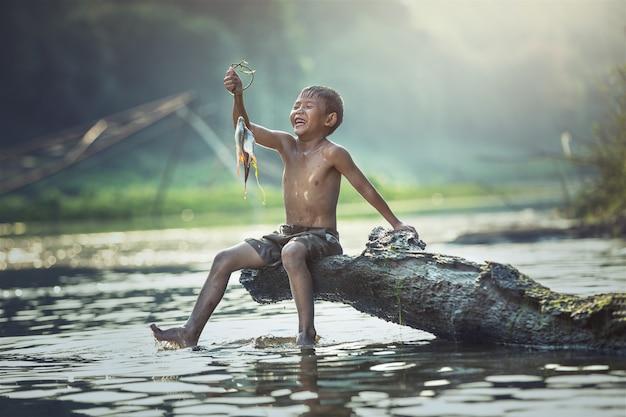 Niño pescando en el río, campo de tailandia