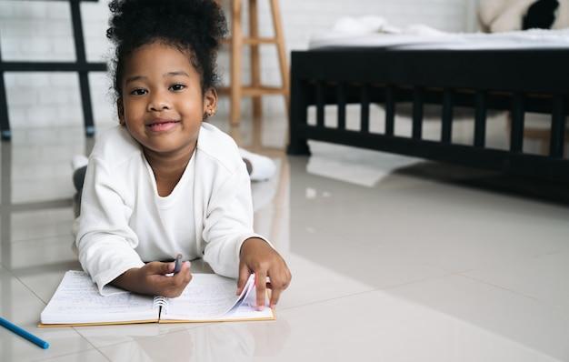 Niño de piel negra con libro en la habitación de la cama