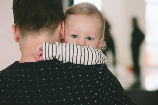 Niño en pijama desnudo mira por encima del hombro del padre