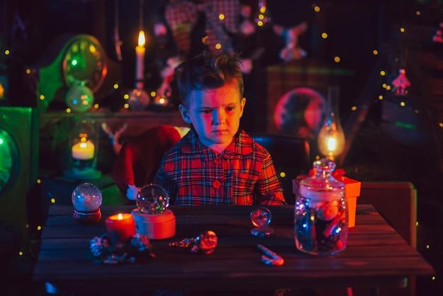 Un niño, con un pijama navideño a cuadros en un ambiente festivo de año nuevo. foto en postal con luz de colores.