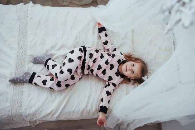Niño en pijama suave y cálido jugando en la cama