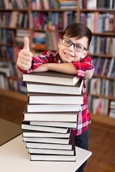 Niño con pila de libros que muestra signo ok