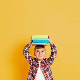 Niño con pila de libros sobre su cabeza.
