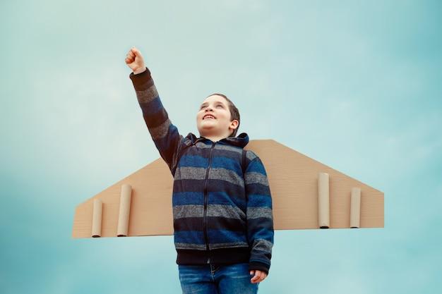 Niño piloto con alas de papel avión jugando y sueños de viajes aéreos
