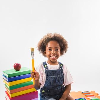 Niño con pincel y libros en estudio