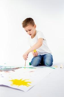 Niño con pincel. niño de 9 años, peinado moderno, camisa blanca, jeans azules dibujando pincel