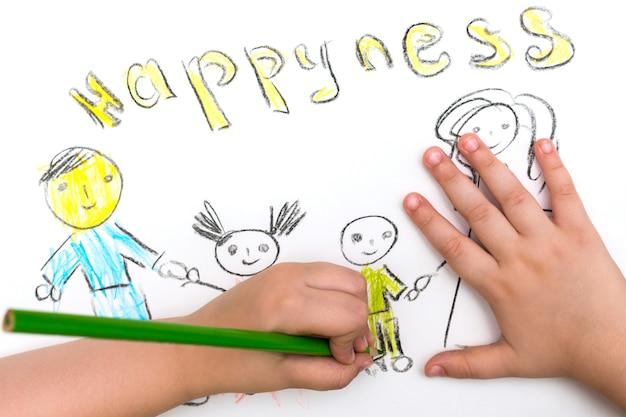 El niño pinta un boceto de la familia.
