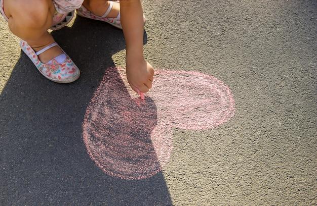 El niño pinta tiza sobre el corazón de asfalto. enfoque selectivo