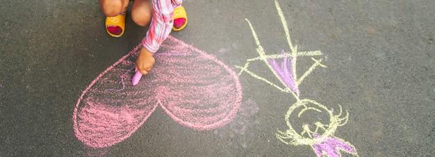 El niño pinta tiza sobre el corazón de asfalto.