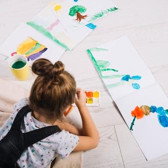 Niño pintando con acuarelas sobre papel y tendido en el suelo.