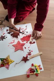 Niño pintando adornos navideños de rodillas en el suelo con una caja de pintura roja festiva, vista superior.
