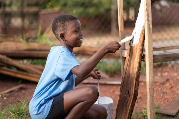 Niño pintando madera de tiro medio